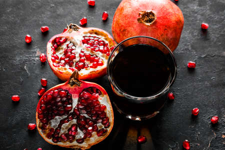 pomegranate juice and fruit on a black background close-up