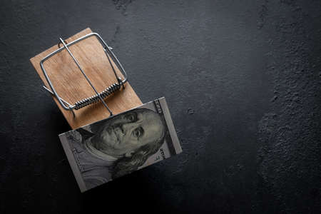 wooden mousetrap with money bait on a black background with place for text Zdjęcie Seryjne