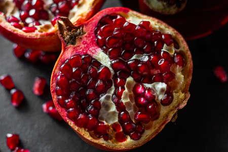 fresh pomegranate fruit and seeds close-up on a black background Zdjęcie Seryjne