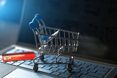 grocery cart on a computer keyboard and credit card on the background of an online store close-up Zdjęcie Seryjne