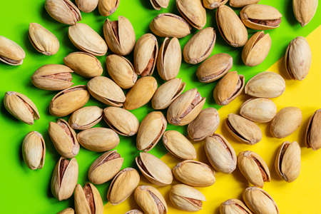 roasted salted pistachios nuts on a colored background close-up