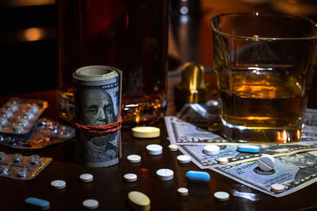 stack of money on the background of alcohol, pills and drugs Zdjęcie Seryjne