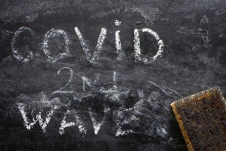 sponge-erased inscription second wave covid on a black background Zdjęcie Seryjne - 156893570