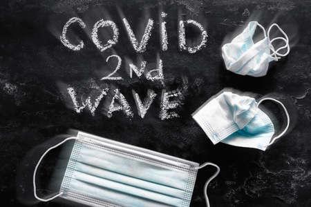 second wave covid lettering on black background and medical masks