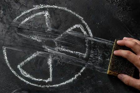 hand with a sponge erases the symbol of nuclear weapons on a black background Zdjęcie Seryjne