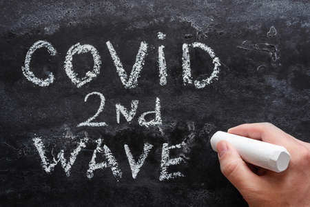 hand with chalk writes second wave covid