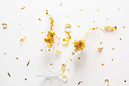 champagne glasses with confetti on white background holiday concept