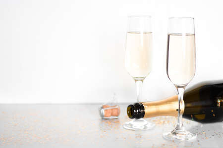 glasses with champagne and a bottle on a white background with place for text holiday concept