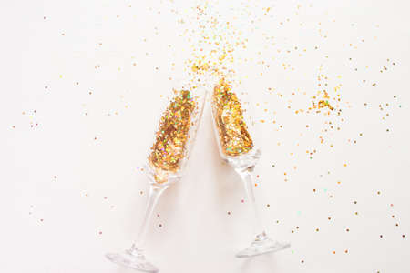 champagne glasses and scattered confetti on a white background. new year holiday concept