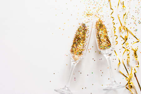 champagne glasses and scattered confetti on a white background with place for text. christmas new year holiday concept Zdjęcie Seryjne