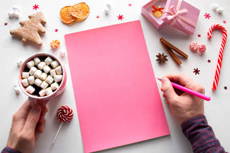 writes a list of New Year wishes on a pink sheet with a mug of coffee with marshmallows mockup