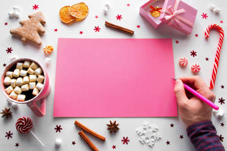 man writes a wish list for the new year on the background of Christmas decorations and sweets mockup