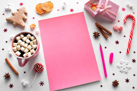 christmas sweets, decorations and pink new year's wishlist with place for text mockup Zdjęcie Seryjne