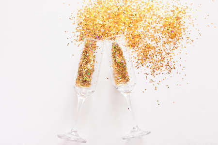 champagne glasses and scattered confetti on a white background. christmas holiday concept