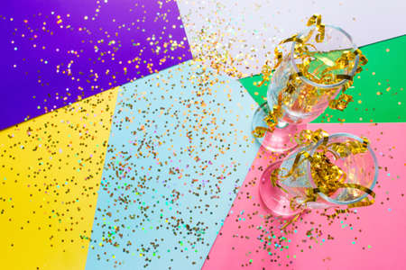 two glasses of champagne with sparkles and tinsel confetti Christmas concept with place for text on a colored background Zdjęcie Seryjne