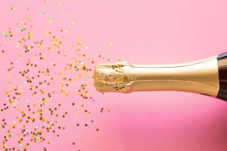a bottle of champagne and a scattering of confetti. Christmas firecracker concept on pink background Zdjęcie Seryjne