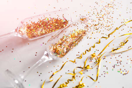champagne glasses with confetti on white background close-up holiday concept