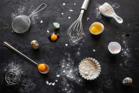 flour, chicken and quail eggs, shape and utensils for baking on a black background