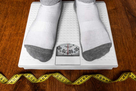 measuring his weight on a scale next to a measuring tape diet weight loss concept
