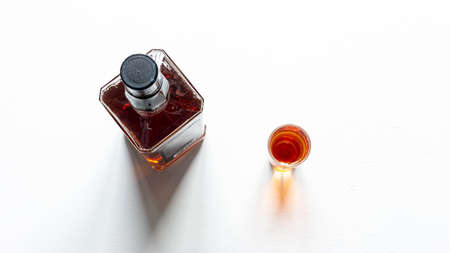 alcohol bottle and glass on white background close up