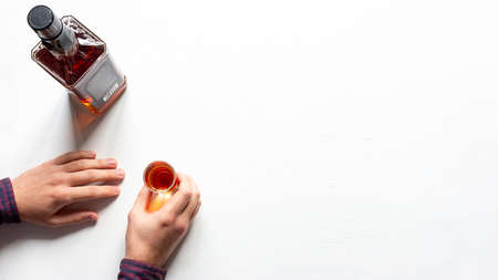 hands hold a glass of alcohol and a bottle of whiskey on a white background with a place for text concept alcoholism Stock fotó