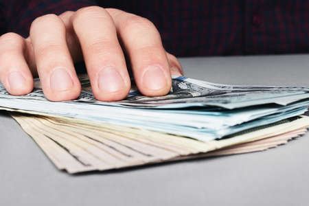 hand and stack of money dollars, giving a bribe close up Stock Photo