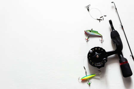 winter fishing rod with reel and lures on white background with place for text