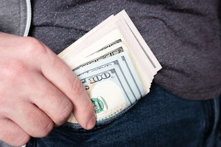 man pulls money out of his pocket close-up Stock Photo