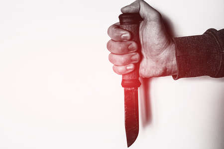 holding knife in hand with red glow crime concept on white background with place for text