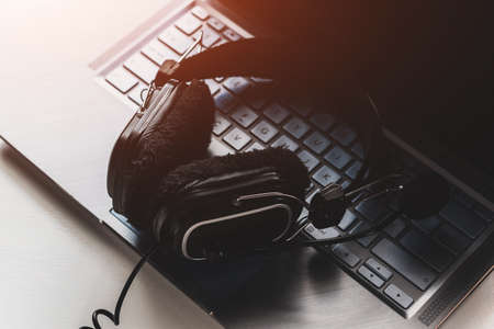 laptop and black headphones with microphone on white background concept of remote work, training, freelance Stock Photo