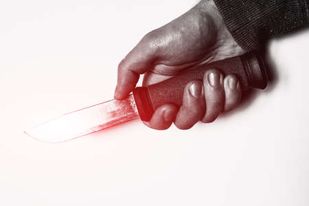 holding knife in hand with red glow concept crime