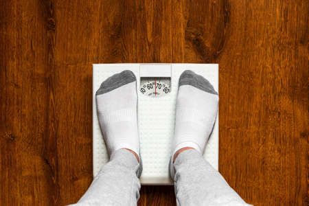man standing on the scales concept healthy eating bodybuilding