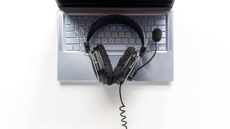 laptop and headphones with microphone on white background concept of remote work, operator, tech support
