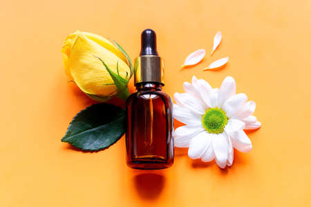 perfume and flowers on an orange background close up