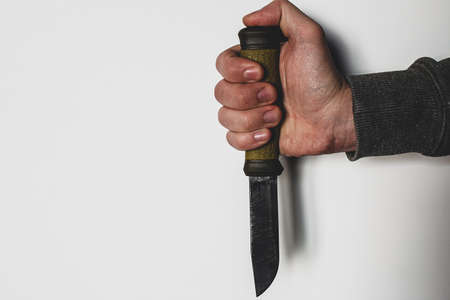 hand and knife on white background with place for text concept of violence, crime