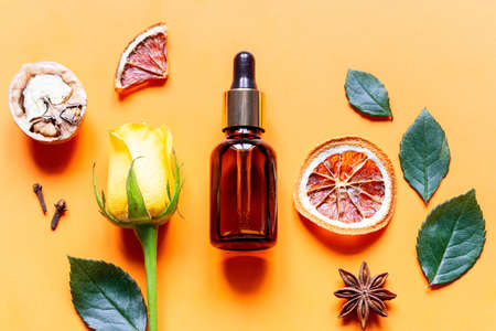perfume and natural ingredients on orange background close up