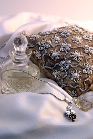 Potpourri cushion, scent bottle and rose necklace on a bed of silk  Stock Photo