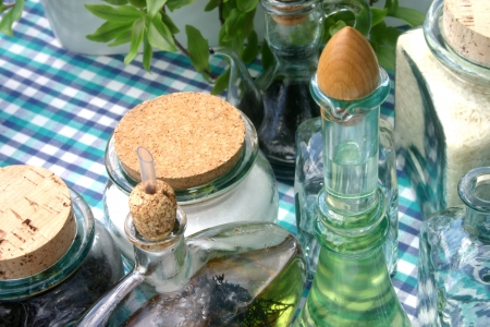 White bowl surrounded by cooking ingredients in glass jars on a checked table cloth