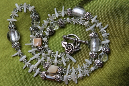 Stone and silver necklace arranged on a background of silk  photo
