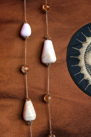 Stone necklace lying on a bronze brown silk material