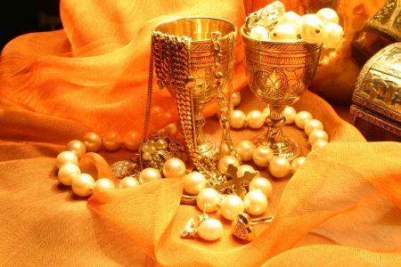 Jewelry and box laying on an orange chifon material photo