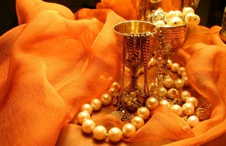 Jewelry laying on an orange chifon material