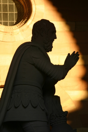 Shadow of statue of praying man Stock Photo