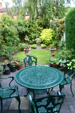 View from terrace with garden furniture of a small formal garden in England
