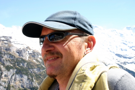 Head and shoulders of a man  with baseball cap and sun glasses  standing in front of swiss alps  Jungfrau near Interlaken