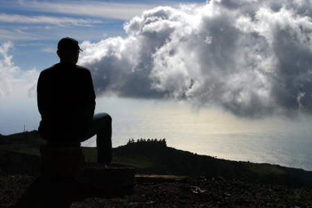 Silhouette of a man on top of mountain looking out to sea on south side of La Gomera, where a large black cloud is passing by  Room for copy  Stock Photo