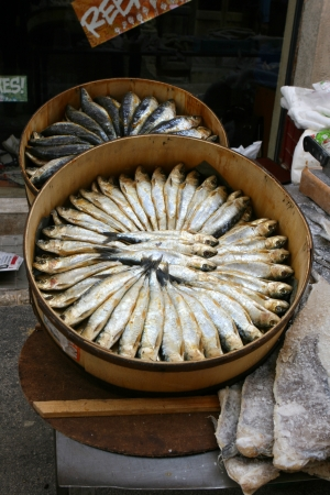 Smoked sardines in a round box on a market stand