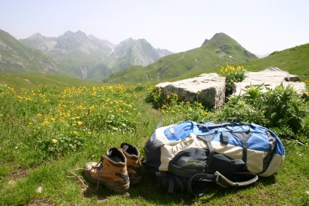 A back pack and walking boots laying in a meadow of yellow flowers in fron of a mountain scene above Lech in Austria  photo