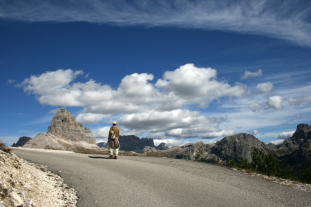Hiker on a mountain road with mountains and skyscape