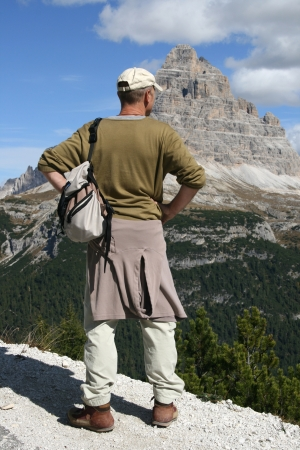 Man in a hooded sweat shirt standing in front of mountains in tirol, Italy